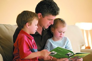 Mid adult man sitting with his two children and reading a book